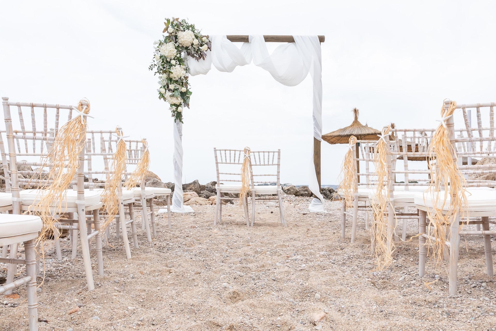 ceremonia blanca en la playa estructura con flores sillas chivary