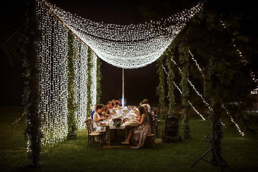 luces de hadas en techo y cortina para cena al aire libre